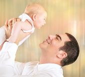Happy father with newborn daughter on playing at home, cheerful dad lifting up little baby on hands,  love and happiness concept