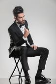 Elegant young man in tuxedo sitting on a stool while snapping his finger, looking away from the came