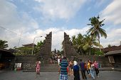 SEPTEMBER 17, 2014 - BALI, INDONESIA: Tourists and devotees enter the temple gates of the Tanah Lot Temple on Bali Island, Indonesia. Balinese practices Hinduism for their religion.
