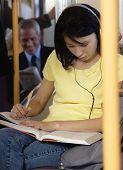 Teenager doing homework on subway