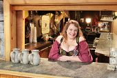 MUSKOGEE, OK - MAY 24: A woman dressed in historic clothing enjoys bartending at the Oklahoma 19th annual Renaissance Festival on May 24, 2014 at the Castle of Muskogee in Muskogee, OK.