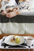 Couples feet laying in bed with breakfast
