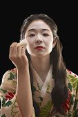 Asian woman in ethnic clothes applying makeup