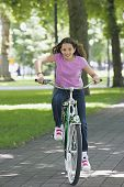 stock photo of pre-adolescents  - Young girl riding a bike - JPG