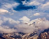 Snowcapped summit top of mountain in Himalayas in clouds. Himachal Pradesh, India