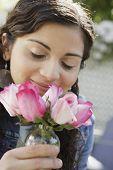 Teenage girl smelling pink roses