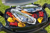 Fresh dorado fish and bell pepper grill cooking outdoors