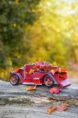 Vintage red truck carrying autumn leaves - concept for change of seasons