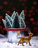 Reindeer ornamental figure with Christmas trees and snow