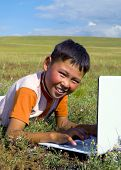 image of mongolian  - Mongolian boy with laptop on grass - JPG