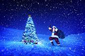 Santa claus holding lantern and sack next to a christmas tree.