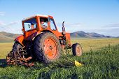stock photo of mongolian  - Mongolian farmer driving his tractor on the field - JPG