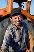 Mongolian farmer standing in front of his tractor reaching forward.