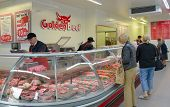 SARLAT, FRANCE - JUNE 28, 2013: People buy meat in the butcher shop Golden Beef. The shop has branches in Limoges, Brive, and Saint-Junien