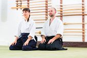 Man and woman at Aikido training in martial arts school