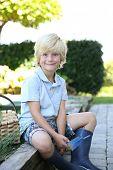 Portrait of cute 7-year-old boy in vegetable garden