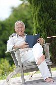 Senior man reading book in pool deck chair