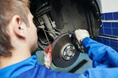 foto of spare  - car mechanic examining car wheel brake disc and shoes of lifted automobile at repair service station - JPG