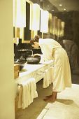 Woman washing her face in spa bathroom