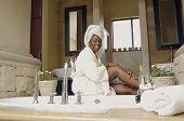 African American woman in bathroom wearing bathrobe