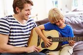 Father Teaching Son To Play Guitar