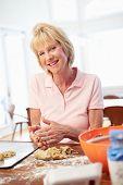 Senior Woman Baking Cookies In Kitchen