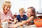 Grandmother And Grandchildren Baking Cookies Together