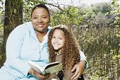 African mother and daughter reading outdoors