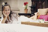 Woman lying on bed with breakfast tray