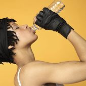 Studio shot of African woman drinking bottle of water