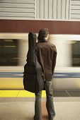 Rear view of man with guitar waiting for train
