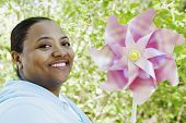 African woman holding pinwheel outdoors