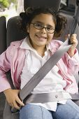 image of seatbelt  - Girl fastening seatbelt in backseat of car - JPG