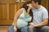 Pregnant couple kissing outdoors