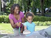 African mother and young daughter washing car