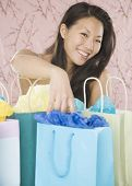 Young Asian woman smiling with shopping bags