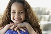 picture of braces  - African girl with braces leaning chin on knees outdoors - JPG