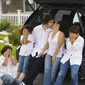 Parents kissing while children cover their eyes