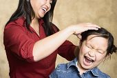 Asian mother fixing yelling daughter's hair