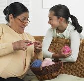 Hispanic grandmother and granddaughter with knitting supplies