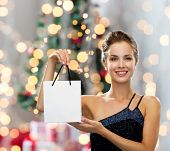 sale, advertisement, holydays and people concept - smiling woman with white blank shopping bag over christmas tree and lights background