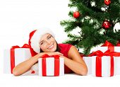 christmas, xmas and happiness concept - smiling woman in santa helper hat with many gift boxes and tree