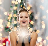 people, holidays and magic concept - laughing woman in evening dress holding something over christmas tree and lights background