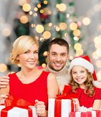 christmas, holidays,  family and people concept - happy mother, father and little girl in santa helper hat with gift boxes over over living room and christmas tree background