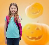 education, holidays, childhood, gesture and people concept - smiling little girl with backpack showing thumbs up over halloween pumpkins background