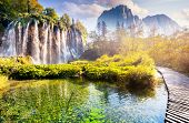 stock photo of waterfalls  - Majestic view on waterfall with turquoise water and sunny beams in the Plitvice Lakes National Park - JPG