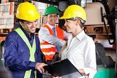 Young female supervisor communicating with foreman at warehouse