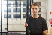 Portrait of confident young male athlete standing at healthclub