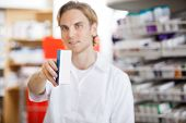 Young Caucasian pharmacist holding out prescription drug