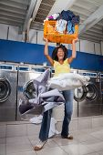 Young woman screaming while carrying overloaded laundry basket at laundromat